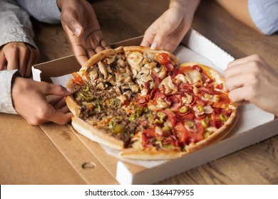 Close up hands of multi-ethnic people hungry students best friends gathered together meet in pizzeria taking sharing slices of meat pizza, girls and guys ordering italian cuisine enjoying food concept