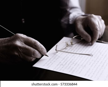 Close up of a hands of an old man, writing in a paper.