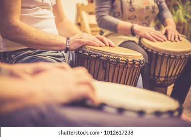 Close up of hands on african drums, drumming for a music therapy (color toned image)