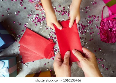 Close up hands of parent giving a red envelope or money red packet to child  .  Chinese new year and Lunar new year festival concept background . Top view .