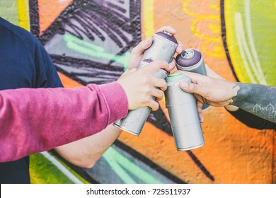 Close up hands of people holding color spray cans against the graffiti wall - Graffiti artists at work - Rebels, lifestyle, street art concept - Focus on can spray on the right
