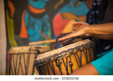 Close up of hands of people playing on African djembe drums