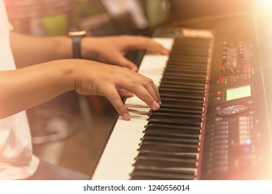 Close up hands of pianist musician playing keyboard synthesizer on  band in night concert selective shallow depth of field
