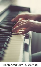 Close up of hands, playing piano. Vintage tone filter effected. Soft focus