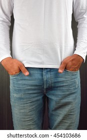 Close up of hands in pockets of blue jeans of young man wearing white blank t-shirt, standing in a studio. Clothing design concept
