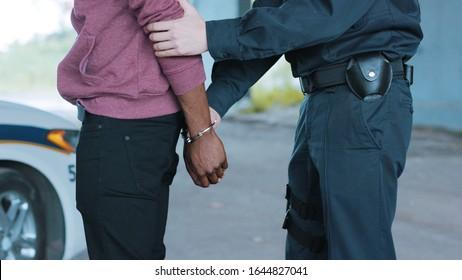 Close up hands policeman arrest man handcuffed criminal handcuffs justice policeman black broadcast robbery burglar drugs guilt illegal job journalist male prisoner slow motion