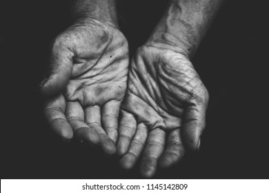 close up hands poor old man or beggar begging you for help sitting at dirty slum. concept for poverty or hunger people,human Rights,donate and charity,background text.lowkey,black and white tone.