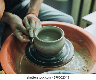 Close up of hands of the potter creating utensils