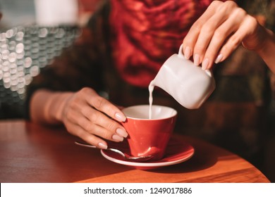 Close up of Woman's hands pouring milk in red coffee cup - woman sitting in cafe with soft drink