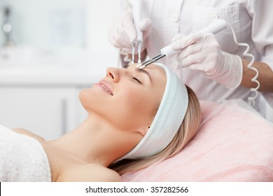Close up of hands of professional beautician touching female forehead with the equipment. The young woman is lying and smiling