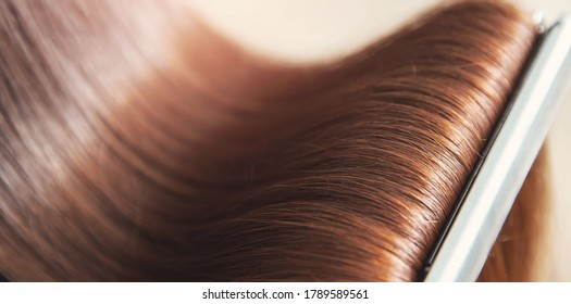 Close up hands of professional hairdresser beauty salon, straighteners curling female hair.