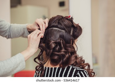 Close up of hands of professional hairdresser at beauty salon, curling female hair