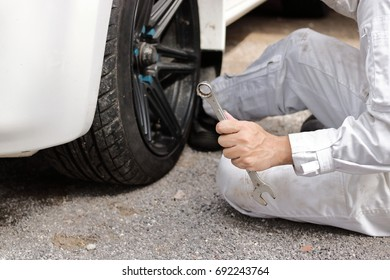 Close up hands of professional mechanic in white uniform holding wrench ready to repairing car at garage.