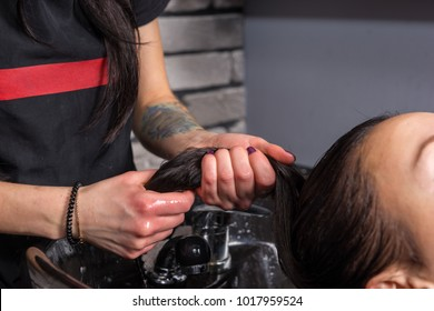 Close up hands of professional stylist washing hair of beautiful woman in washing sink in beauty salon