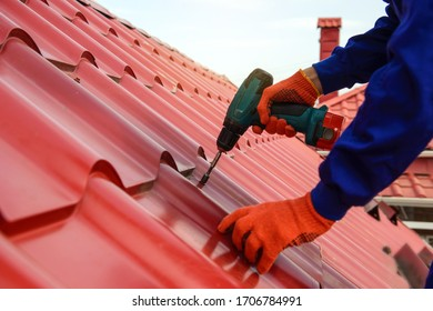 Close up hands in protective gloves of young man worker who fix a metal tile roof with screwdriver. Roofing work concept