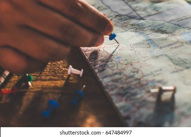 Close up hands putting pins to destination on world map. young male planning vacation. backpack travelling concept.
