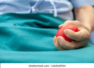 close up of hands senior man or patient doing exercise with rubber ball or squeezing a stress ball or small red heart for Loosen the muscles and The blood flow better. health, medicine, people concept