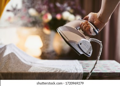 Close up hands of senior woman ironing clothes using steam. Steaming washed laundry. Visiting mom. Home chores of an elderly person. Self-isolation for the elderly