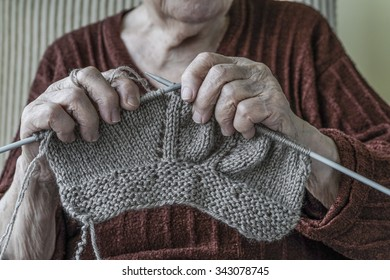 close up hands of a senior woman knitting