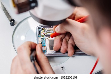 Close up hands of a service worker repairing modern smarphone. Repairing and service concept.