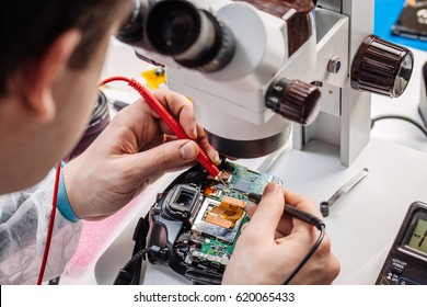Close up hands of a service worker repairing digital camera. Repairing and sservice concept.