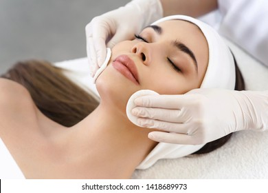 Close up of hands of skillful beautician cleaning and touching female face with cotton pad or sponge. The woman is lying and relaxing. Her eyes are closed with pleasure