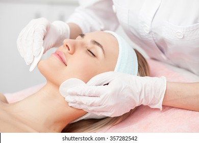 Close up of hands of skillful beautician cleaning and touching female face with sponge. The woman is lying and relaxing. Her eyes are closed with pleasure