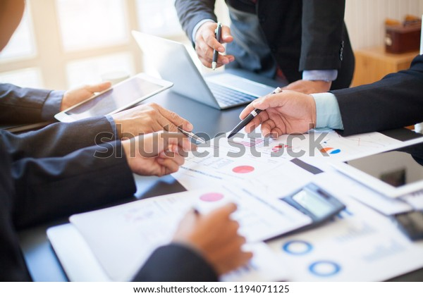 Close up of hands and stationery of Business people counting on calculator sitting at the table