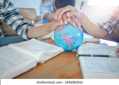 Close up hands of three christian praying for globe and people around the world on wooden table with bible.
