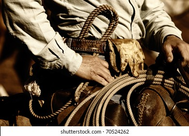 Close up of the hands and torso of an authentic working cowboy in the American West riding to work in sunset light (sepia/brown tint).