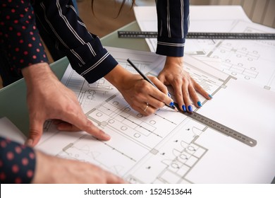 Close up with the hands of two architects who draw something in a house plan. blueprints and new construction plan