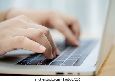 Close up hands typing on laptop keyboard.
