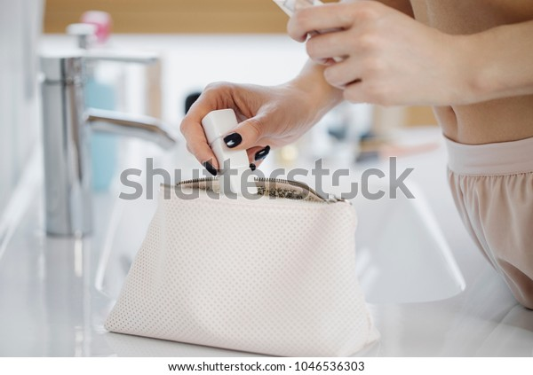 Close up of hands of unrecognisable woman taking make-up products from her cosmetic bag.