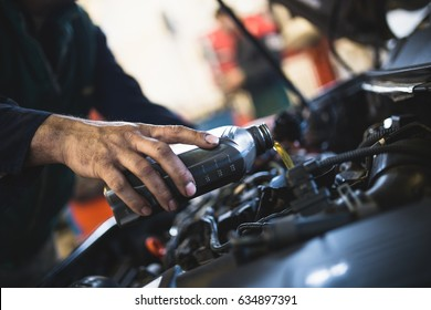 Close up hands of unrecognizable mechanic doing car service and maintenance. Oil and fuel filter changing.