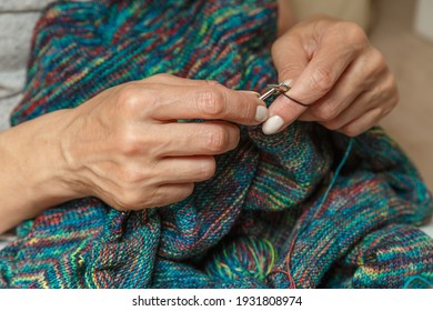 Close up of hands of unrecognizable woman knitting handmade clothes with spokes using  wool yarn. Concept of leisure activity.Knitting from yarn on  coarse spokes.