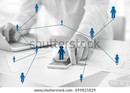 Close up of hands using mobile phone, laptop and employees icons in black-and-white style.Concept of human resources management