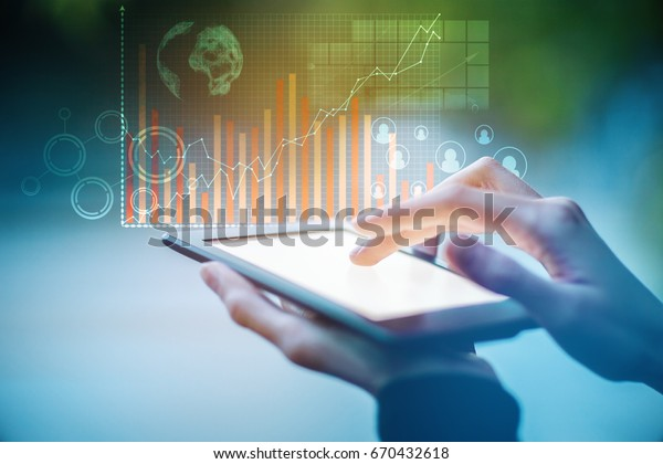 Close up of hands using tablet with abstract digital business hologram on blurry blue background. Tech concept