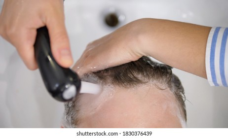 Close up of hands washing hair in hair salon. Beauty and self care concept.