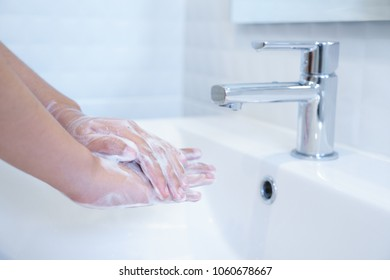 Close up of hands washing with soap in sink