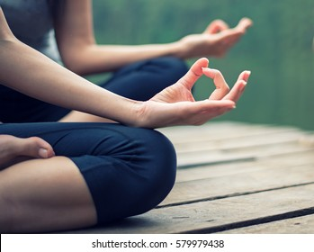 Close up hands. Woman do yoga outdoor. Woman exercising for meditation yoga at the nature background.  Healthy Concept