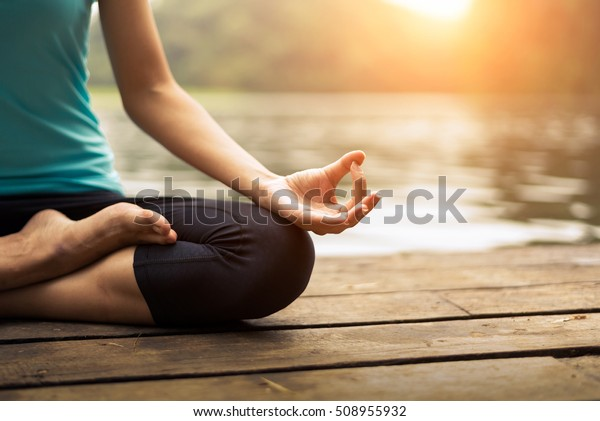 Close up hands. Woman do yoga relax outdoor. Woman exercising pose vital and meditation for fitness lifestyle club at the outdoors nature background. Healthy and Yoga Concept