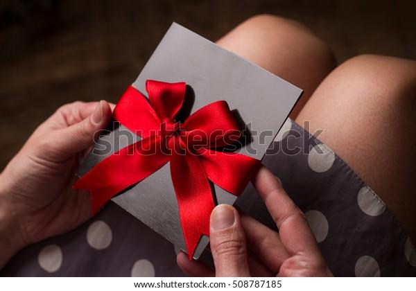Fechar as mãos de uma mulher com vestido de polca segurando um cartão preto com fita vermelha acima dos joelhos