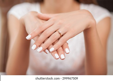 Close up of hands of woman showing the ring with diamond. She is engaged