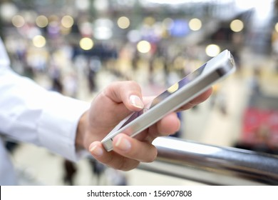 Close up of hands woman using her cell phone in train station, background people
