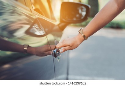 Close up hands woman using systems key near car for lock,unlock of blue hatchback car near street road driving.