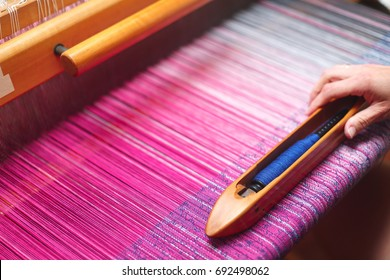 Close up hands of woman weaving color pattern on loom