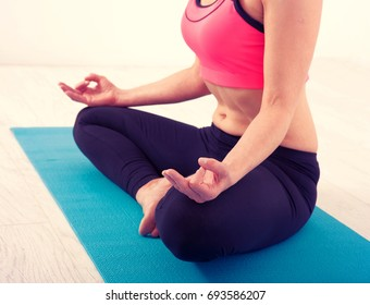 Close up hands. Women do yoga indoors. Woman exercising yoga at sunset with warmth background in gym. Young woman conducts meditating indoors.