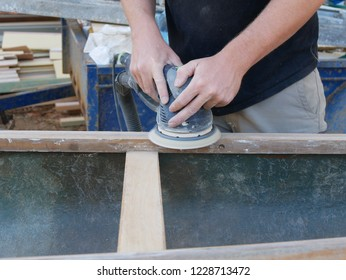Close up of the hands of a working man using a power tool with a rotating disc to sand the hard wood gunwales of a fibreglass canoe that is being restored in East Gipssland, Victoria, Australia