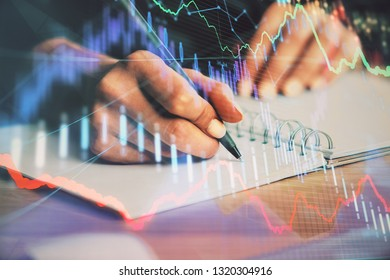 Close up of hands writing with double exposure of business charts. Financial concept.