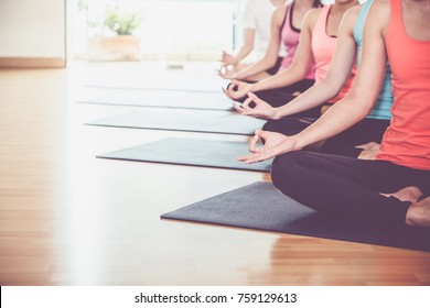 Close up hands of yoga group seated doing Hand Mudra and meditates in a training studio fitness room, Calm and relax concept,wellness and healthy lifestyle,leave space for adding text
